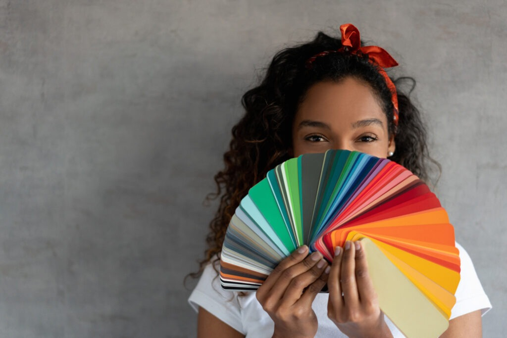 A woman holds a fanned-out set of various color card samples.