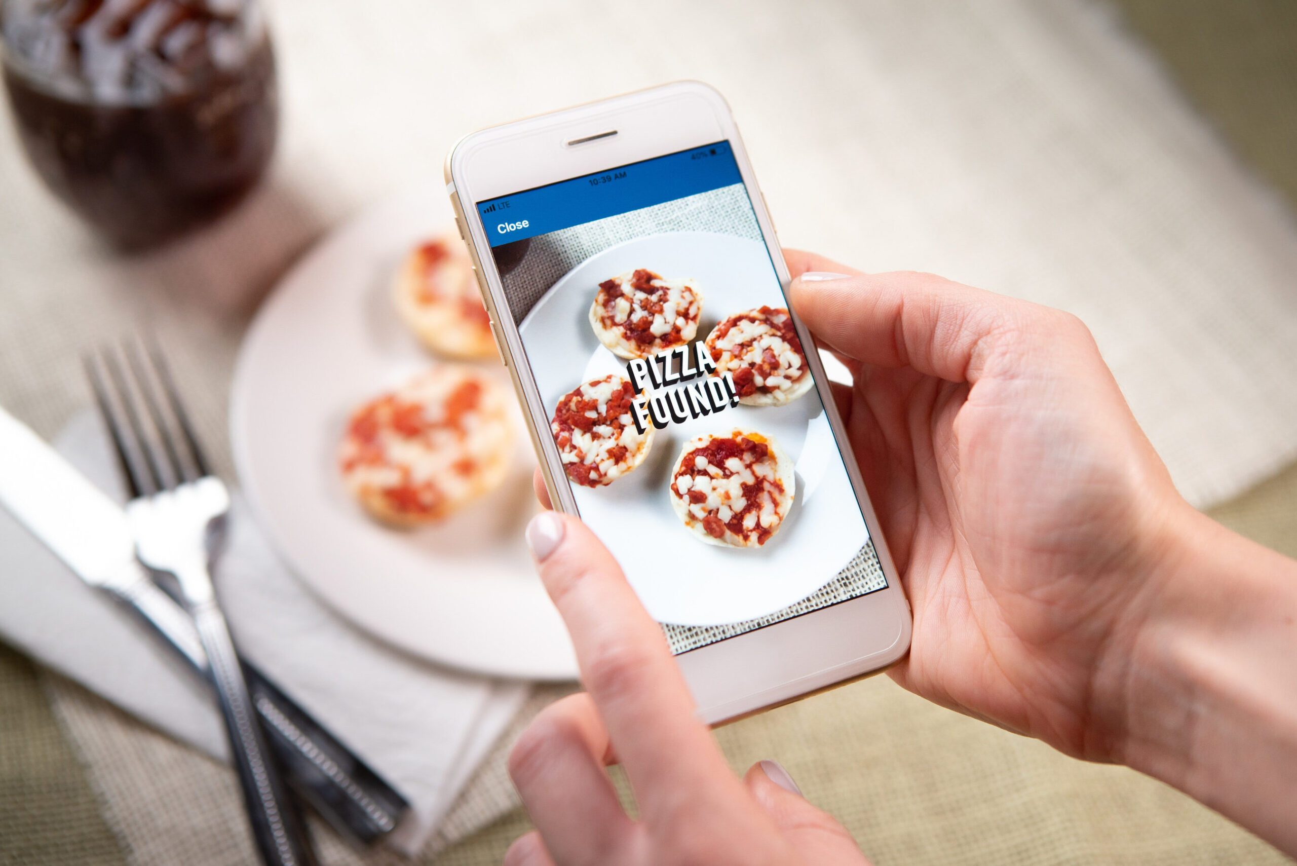 Person holding cell phone with opened app that will scan their pizza for further information.